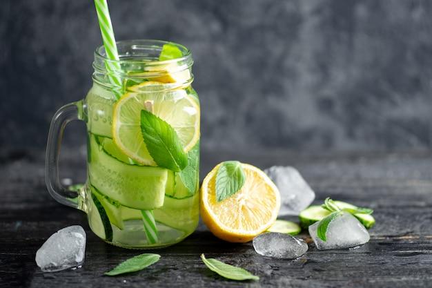 Vaso di vetro di limonata estiva con acqua fredda dietetica di menta e limone e cetriolo
