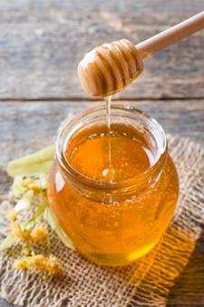 Vaso di vetro di miele, fiori di tiglio su superficie di legno