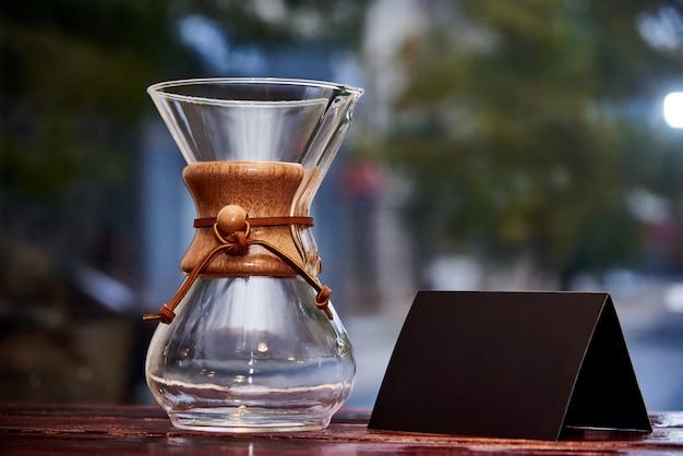 Vaso di vetro e carta nera su una superficie di legno.