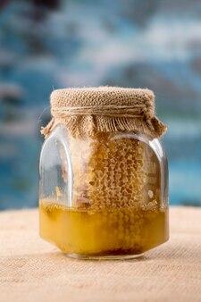 Vaso di vetro miele con polline d'api, favi