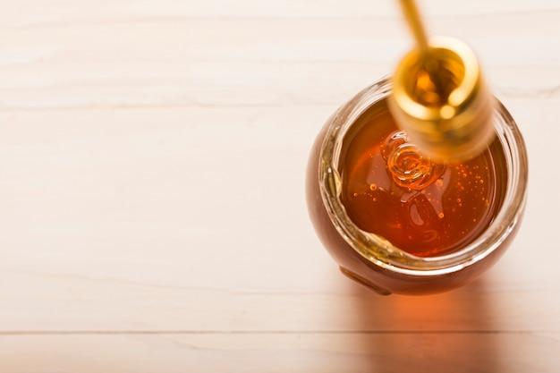 Vaso di vetro pieno di miele con cucchiaio di miele