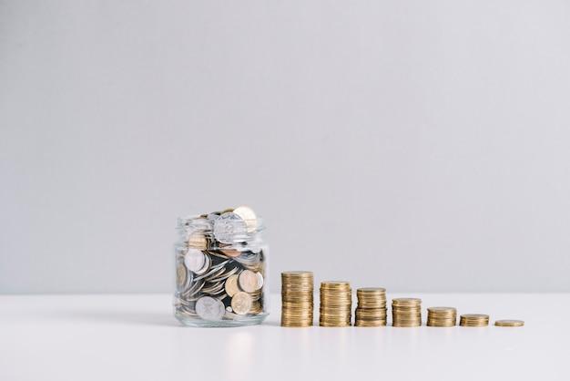 Vaso di vetro pieno di soldi davanti a monete impilate decrescente su sfondo bianco