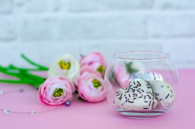 Vaso di vetro trasparente con biscotti a forma di cuore e fiori su sfondo rosa.