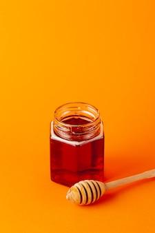 Vaso e mestolo del miele dell'angolo alto con lo spazio della copia
