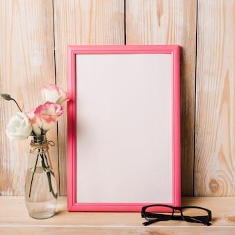 Vaso e occhiali vicino alla cornice bianca sulla scrivania