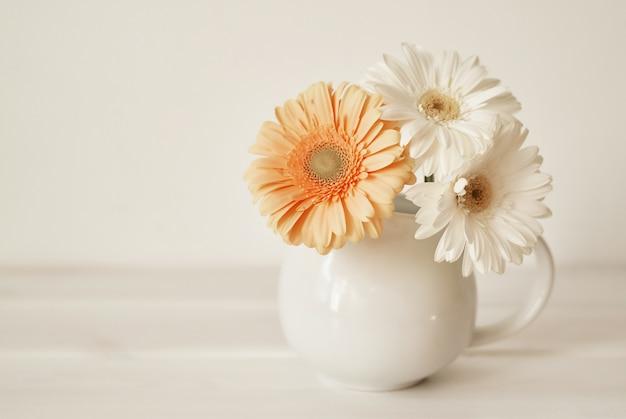 Vaso in ceramica con fiori di gerbera. cartolina di primavera nella festa della mamma con fiori,