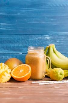 Vaso per frullato vista frontale con banane e arance