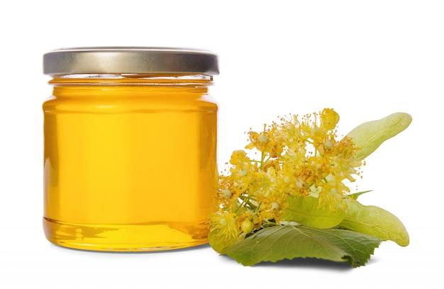 Vaso pieno con miele di tiglio e tiglio fiorito su bianco
