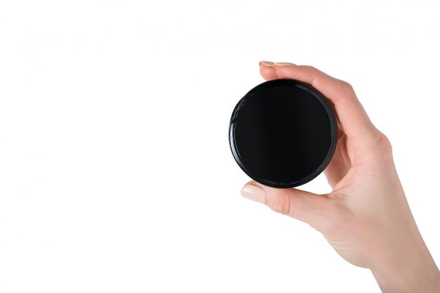 Vaso rotondo nero per crema e cosmetici in una mano femminile. isolato su bianco direttamente sopra