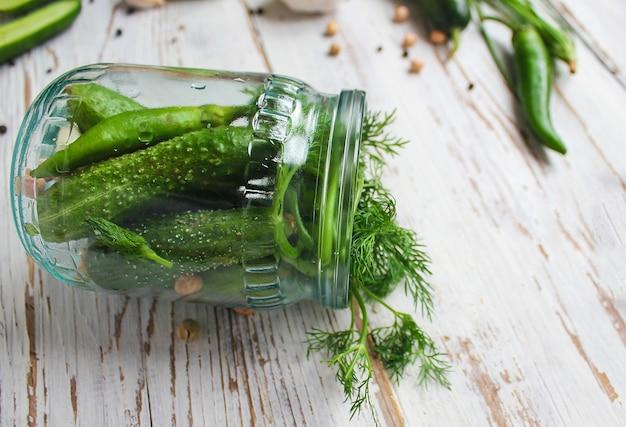 Vaso sottaceti di cetrioli biologici freschi sul tavolo di legno bianco con verde e rosso e peperoncino, finocchio, sale, grani di pepe neri, aglio, pisello, pomodori verdi, da vicino, concetto sano, vista dall'alto, piatto