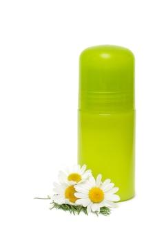 Vaso verde di un deodorante e di un fiore isolati su bianco
