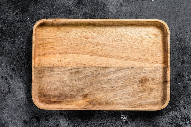 Vassoio antico in legno. sfondo nero testurizzato. vista dall'alto. copia spazio