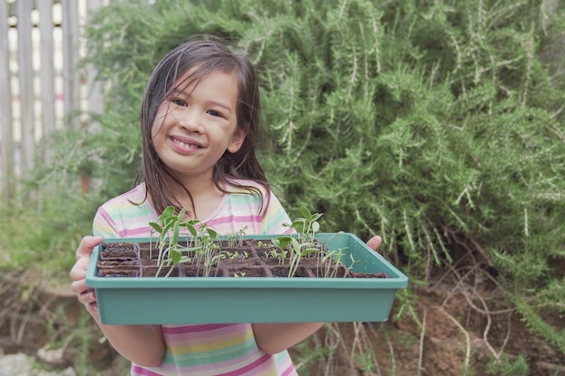 Vassoio asiatico misto felice della piantina della tenuta della ragazza, giardinaggio di verdure, attività all'aperto di divertimento, vita sostenibile, concetto di allontanamento sociale