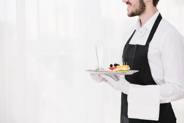 Vassoio barbuto della tenuta del cameriere con lo spazio della copia