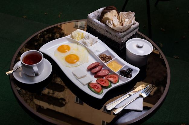 Vassoio colazione con uova fritte, salsicce, formaggio, marmellata e una tazza di tè.