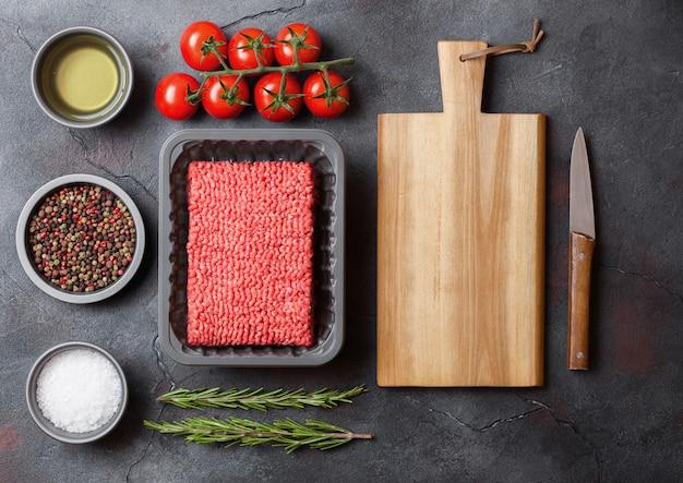Vassoio con carne di manzo fatta in casa tritata cruda con spezie ed erbe aromatiche. vista dall'alto.