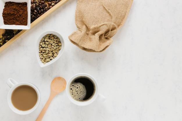 Vassoio con chicchi di caffè e tazze di caffè