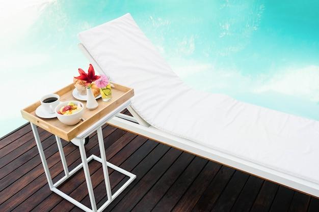 Vassoio con colazione nel tavolino e lettino vicino alla piscina