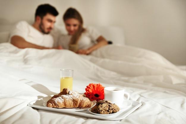 Vassoio con deliziosi caffè, croissant, succo e biscotti si trova sul letto prima di una coppia guardando il telefono