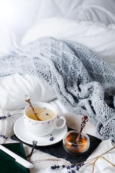 Vassoio con miele e una tazza di tè caldo nel letto