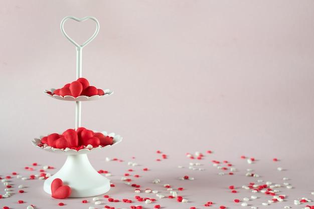 Vassoio da portata bianco a due piani pieno di cuori di caramelle di zucchero. concetto di amore e san valentino.