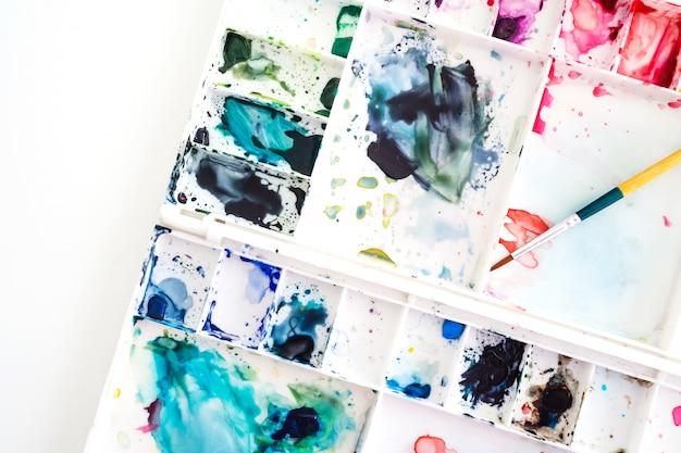 Vassoio dell'acquerello con pennello. arte e sfondo astratto. vista dall'alto.