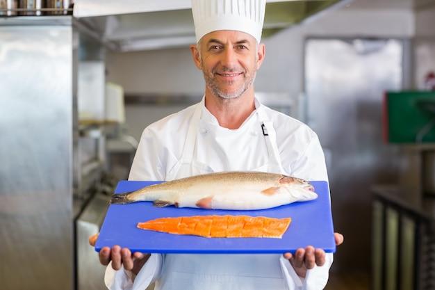 Vassoio della tenuta del cuoco unico di fiducia di pesce crudo in cucina