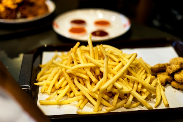 Vassoio di cibo spazzatura pepite di pollo fast food e patatine fritte
