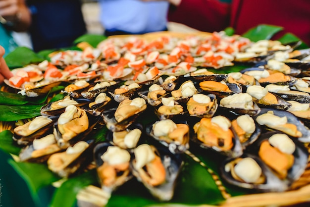 Vassoio di cozze cotte con spezie servite ad una festa gastronomica.
