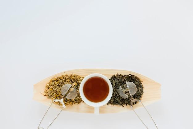 Vassoio di legno con le foglie di tè e lo spazio della copia
