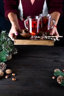 Vassoio di legno con vin brulé caldo fatto in casa con frutta e spezie in mani femminili su un buio