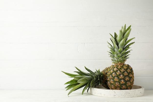 Vassoio di marmo con gli ananas su fondo di legno bianco, spazio per testo