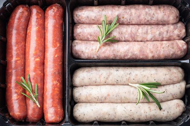 Vassoio di plastica con carne fresca di maiale cruda e salsicce di manzo con rosmarino
