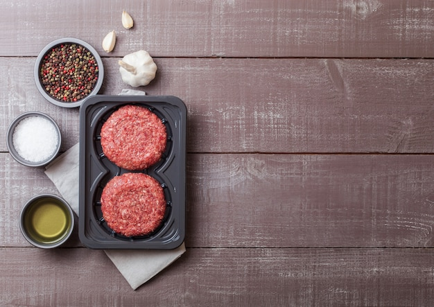 Vassoio di plastica con hamburger di manzo alla griglia tritato crudo fatto in casa con spezie ed erbe aromatiche. vista dall'alto