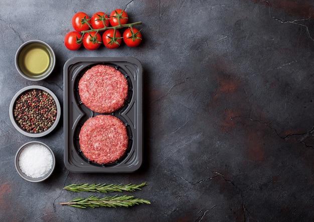 Vassoio di plastica con hamburger di manzo di carne macinata cruda fatta in casa con spezie ed erbe aromatiche. vista dall'alto e.