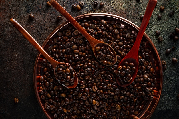 Vassoio di rame rotondo, cucchiai di legno pieni di chicchi di caffè kopi luwak su superficie scura, vista dall'alto