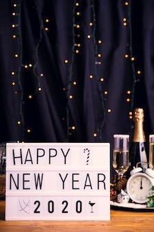 Vassoio di vista frontale con bevande e segno per il nuovo anno