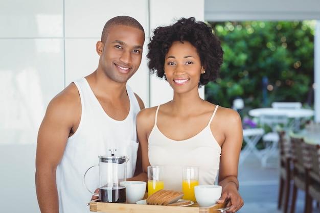 Vassoio felice della prima colazione della tenuta delle coppie nella cucina a casa