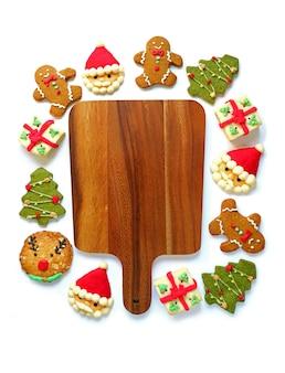 Vassoio in legno circondato con una varietà di biscotti di natale su uno sfondo bianco