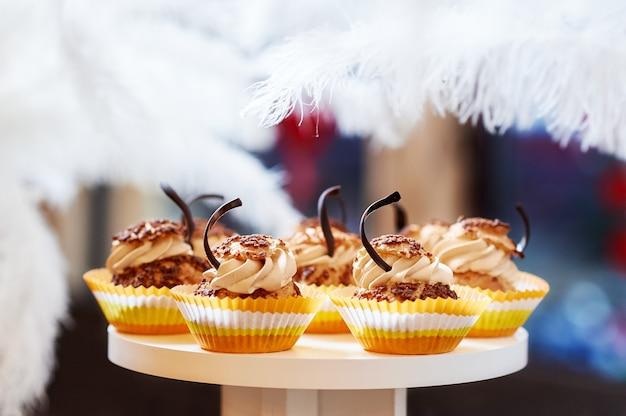 Vassoio in legno con gustosi dolcetti alla vaniglia e cupcakes appena sfornati con decorazioni in crema e cioccolato.