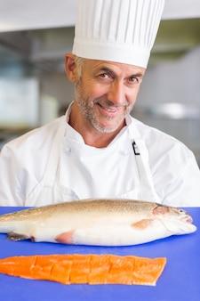Vassoio maschio sorridente della tenuta del cuoco unico di pesce crudo in cucina