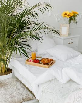 Vassoio per la colazione messo sul letto singolo con biancheria da letto bianca