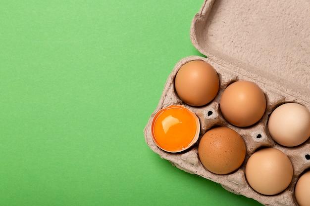 Vassoio per uova su sfondo verde brillante con uovo rotto, tuorlo d'uovo, copia spazio, vista dall'alto