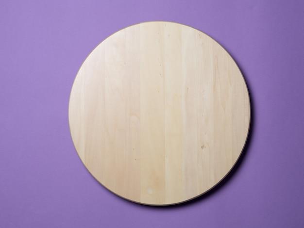 Vassoio rotondo di legno vuoto su fondo lilla