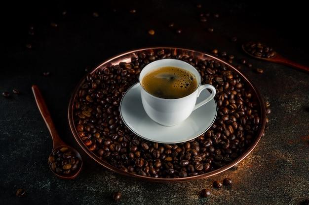 Vassoio rotondo in rame con chicchi di caffè kopi luwak, cucchiai di legno, tazza di caffè bianca con piattino su superficie scura