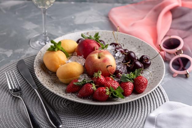 Vassoio sano della frutta, fragole, mele, pesche, albicocche su una tavola di legno grigio scuro, vista superiore, primo piano, fuoco selettivo.