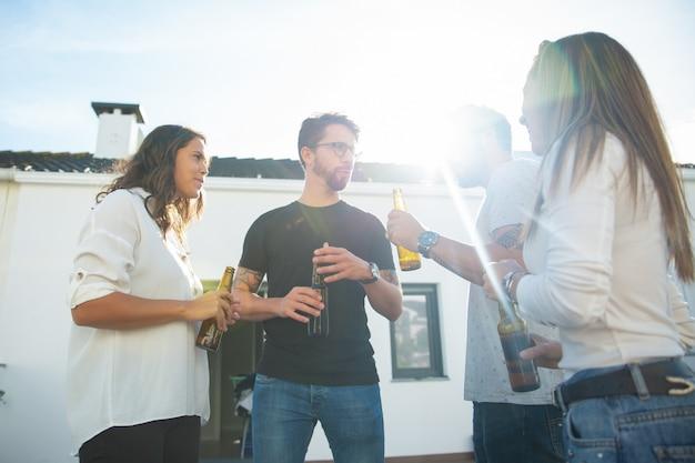 Vecchi amici chiacchierando, bevendo birra e divertendosi