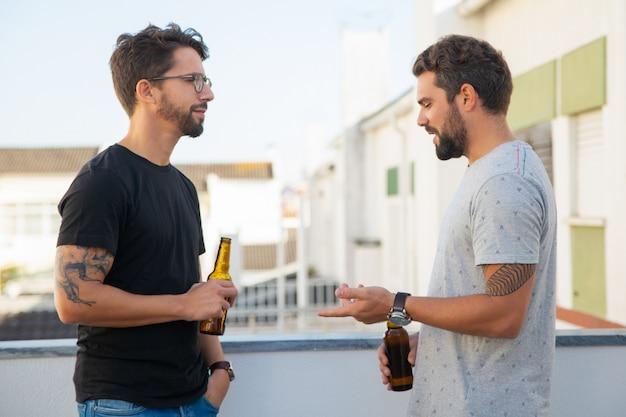 Vecchi amici maschii che bevono birra e conversazione
