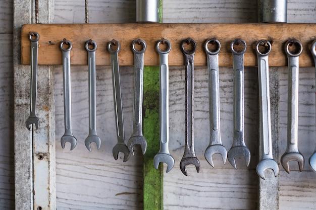 Vecchi attrezzi per bricolage che appendono sulla parete in officina