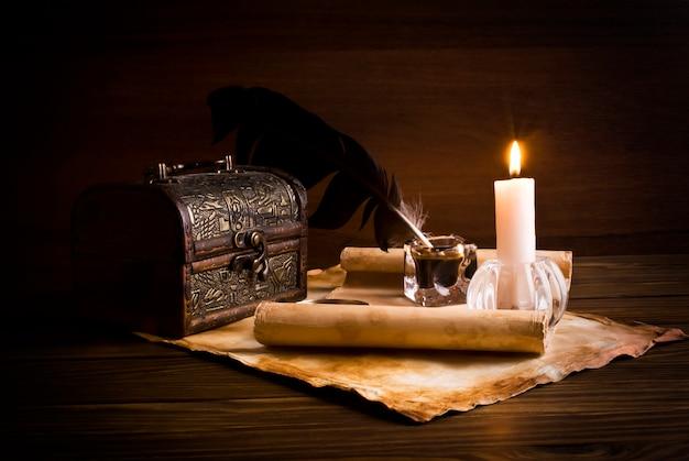 Vecchi documenti su un tavolo di legno accanto alla candela accesa